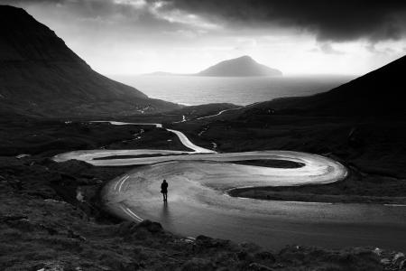 A person stands on a windy road in the Faroe Islands