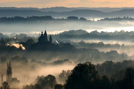 Collonges-la-Rouge backlit on a misty morning, Correze, France