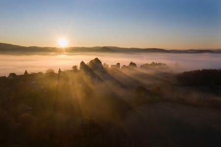 Curemonte backlit at sunrise in the mist, Correze, France