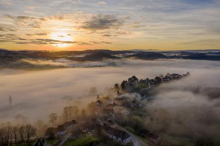 Aerial view of Curemonte surrounded by mist at sunrise, Correze, France