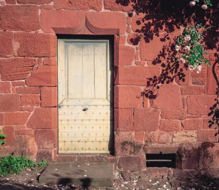 Door and roses in Collonges-la-Rouge, Correze, France