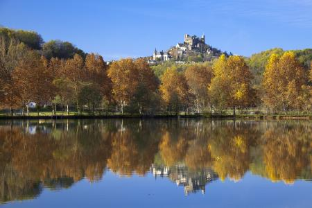 Turenne reflected in a lake in the autumn; Correze, France