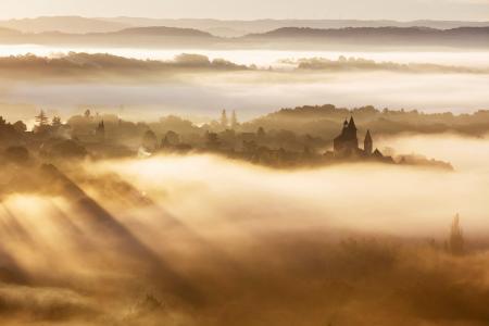 Collonges-la-Rouge village backlit on a misty morning, Correze, France